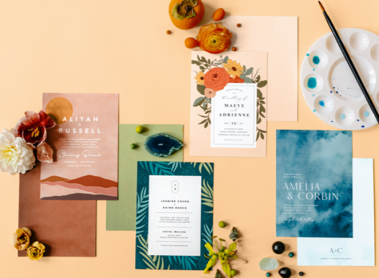 Four wedding invitations including a mountain invitation, a blue watercolor invitation, a floral invitation and a tropical palm invitation.